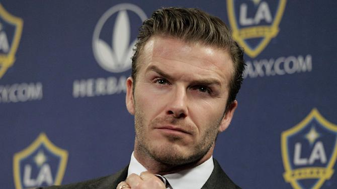FILE - In this Jan. 19, 2012 file photo, Los Angeles Galaxy's David Beckham fixes his tie during a news conference in Los Angeles. Beckham says he is retiring from soccer at the end of the season. The 38-year-old Beckham recently won a league title in a fourth country with Paris Saint-Germain. He has become a global superstar since starting his career at Manchester United.  (AP Photo/Jae C. Hong, File)