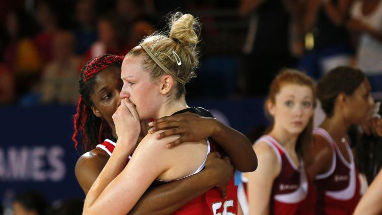England's Agbeze consoles teammate Harten after their loss to Australia in their Netball Preliminary Round at the 2014 Commonwealth Games in Glasgow