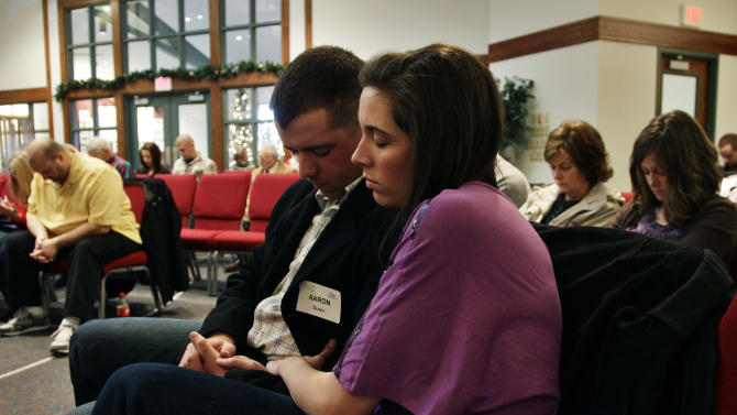 """In this Dec. 23, 2012 photo, three weeks back home from the war in Afghanistan, U.S. Army 1st Lt. Aaron Dunn and his wife Leanne pray during services at their church, in Colorado Springs, Colo. On war and coming home, Dunn says: """"War and coming home are going to mean different things to each soldier. For me it was God and Family. I get my security in life from my hope in God, and my companionship and support from my family."""" (AP Photo/Brennan Linsley)"""