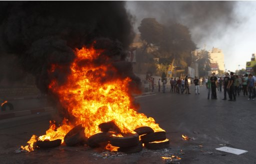 Palestinians stand near burning tyres during a protest against the high cost of living in Nablus