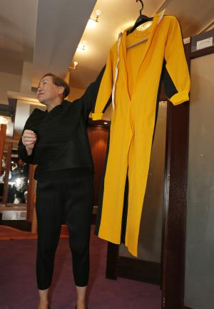 """Anna Lee, vice-chairman of Spink auction house, holds Bruce Lee's original yellow jumpsuit he wore in """"Game of Death"""" during an auction preview in Hong Kong, Monday, Dec. 2, 2013. It's part of a collection of 14 items including clothing and props going on the block on Thursday. Lee died in 1973, before the movie was finished. Spink estimates the suit will fetch 250,000 to 300,000 Hong Kong dollars ($32,250-$38,700). (AP Photo/Vincent Yu)"""