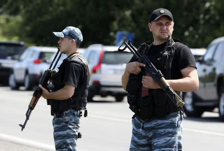 Armed pro-Russian separatists stand guard on the suburbs of Shakhtarsk