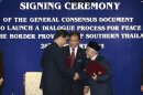 Pattanathabutr of Thailand's NSC and Hassan of Thailand's BRN liason office in Malaysia shake hands as they exchange documents during a signing ceremony in Kuala Lumpur