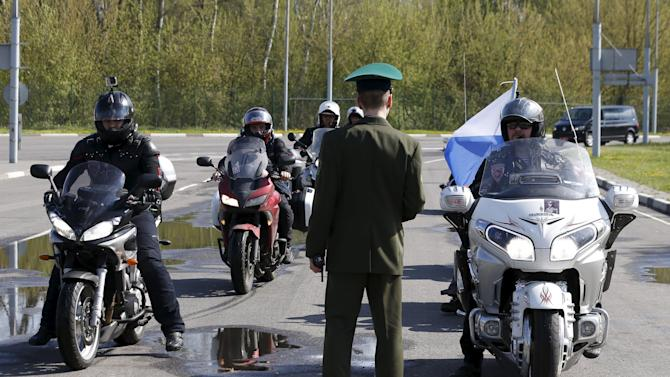 Belarussian border guard stand in front of participants of bike ride at border crossing with Poland near Brest