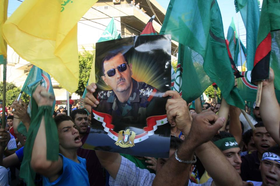 Hezbollah supporters carry banners and wave Iranian and Hezbollah flags along Syrians holding pictures of Syrian President Bashar Assad during a march organized by Hezbollah denouncing an anti-Islam film that has provoked a week of unrest in Muslim countries worldwide in the southern city of Tyre, Lebanon, Wednesday, Sept. 19, 2012. (AP Photo/Mohammed Zaatari)