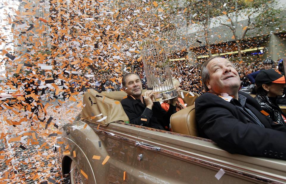 San Francisco Giants manager Bruce Bochy holds the World Series trophy as confetti falls during the baseball team's World Series victory parade, Wednesday, Oct. 31, 2012, in San Francisco. (AP Photo/Jeff Chiu)