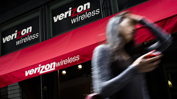 FILE - In this Thursday, June 6, 2013, file photo, a pedestrian uses her cell phone as she passes a Verizon Wireless store on Broadway in Lower Manhattan, in New York. Verizon Communications Inc. reports quarterly financial results before the market opens on Thursday, July 18, 2013. (AP Photo/John Minchillo, File)