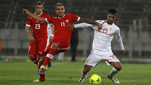 Tunisia's Abdelkader Oueslati (R) fights for the ball with Switzerland's Behrami Valon (Reuters)