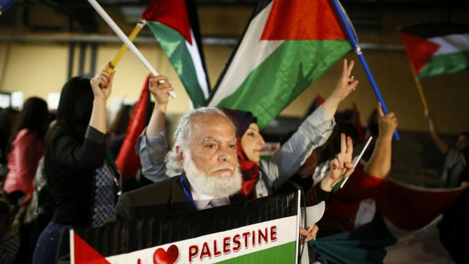 People hold Palestinian flags during the Conference of Palestinians in Berlin