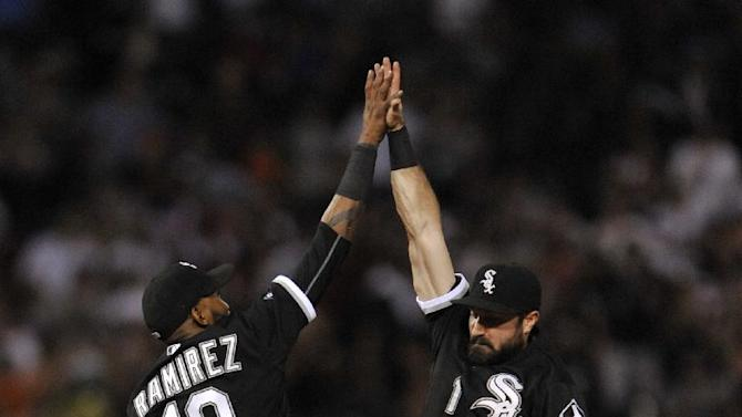 Chicago White Sox's Alexei Ramirez (10), celebrates with teammate Adam Eaton (1), while Melky Cabrera (53), looks on after defeating the Toronto Blue Jays 4-2 in a baseball game Monday, July 6, 2015 in Chicago. (AP Photo/Paul Beaty)