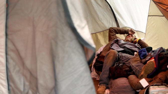 FILE - In this file photo of Nov. 20, 2012 photo, Anthony Gatti makes a call while resting in a tent where he is living in the Midland Beach section of the Staten Island borough of New York. The image of his brother trapped in a car with water rising to his neck, his eyes silently pleading for help, is part of a recurring nightmare that wakes Anthony Gatti up, screaming, at night. Gatti hauled his brother out of the car just in time, saving his life at the height of Superstorm Sandy. The two men rode out the hurricane in their childhood home and survived. But weeks afterward, Gatti still hasn't moved on. He's still living in a tent in the backyard, burning pieces of furniture as firewood, refusing to leave the site of his home until the place is demolished. (AP Photo/Seth Wenig, File)