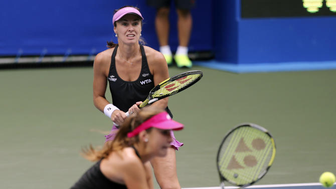 Martina Hingis, rear, and Belinda Bencic both from Switzerland, play against Zimbabwe's Cara Black and Sania Mirza of India during their doubles quarterfinal match of the Pan Pacific Open Tennis tournament in Tokyo Thursday, Sept. 18, 2014. (AP Photo/Koji Sasahara)