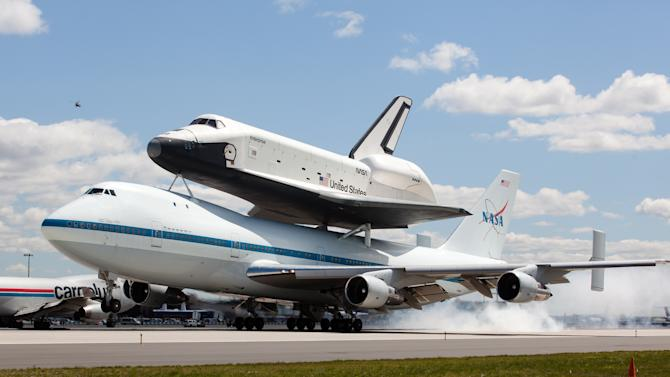 Space shuttle Enterprise, riding on the back of the NASA 747 Shuttle Carrier Aircraft, lands at JFK International Airport, Friday, April 27, 2012, in New York.  Enterprise is eventually going to make its new home in New York City at the Intrepid Sea, Air and Space Museum. (AP Photo/John Minchillo)