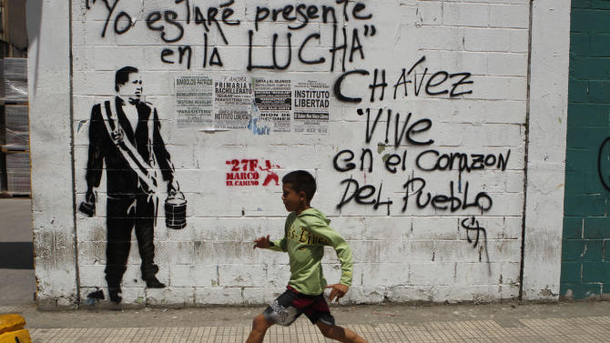 "A child runs past a wall with a stencil graffiti of Venezuela's late President Hugo Chavez and spray-painted writing that reads in Spanish; ""I will be present in the fight. Chavez lives in the heart of the people,"" in Caracas, Venezuela, Thursday, March 7, 2013. Battling an unspecified cancer, Chavez died Tuesday. His body was taken to the military academy Wednesday, where he started his army career, his flag-draped coffin lying in state as a mile-long line of mourners came to pay homage Thursday. (AP Photo/Esteban Felix)"
