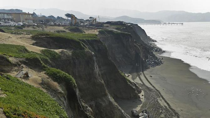 In this photo taken on Wednesday, Feb. 3, 2016, large boulders await placement at the base of eroding cliffs in Pacifica, Calif. Pacifica, which means peaceful in Spanish, is anything but that when heavy rains and big surf batter this largely working class city of roughly 40,000, about 10 miles south of San Francisco. The area is one of the two most erosion-prone stretches of the state's coastline (AP Photo/Ben Margot)