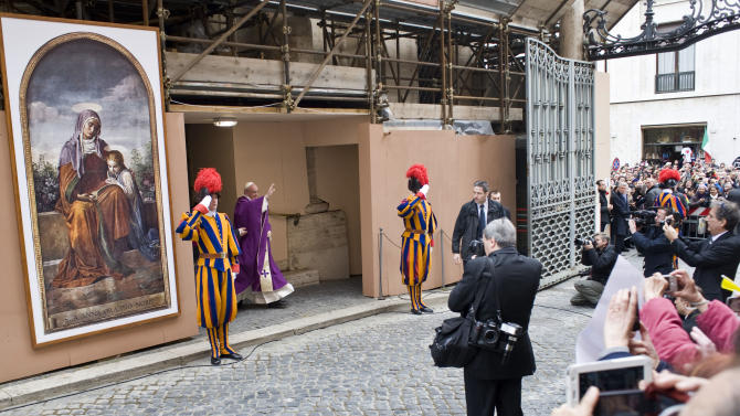 Pope Francis greets faithful at the Vatican, Sunday, March 17, 2013. Pope Francis began his first Sunday as pontiff by making an impromptu appearance to the public from a side gate of the Vatican, startling passersby and prompting cheers, then kept up his simple, spontaneous style by delivering a brief, off-the-cuff homily at the Vatican's tiny parish church. Dressed only in white cassock, Francis waved to the crowd in the street outside St. Anna's Gate and before entering the church, which serves Vatican City State's hundreds of residents, he shook hands of the parishioners and kissed babies. (AP Photo/Antonello Nusca)