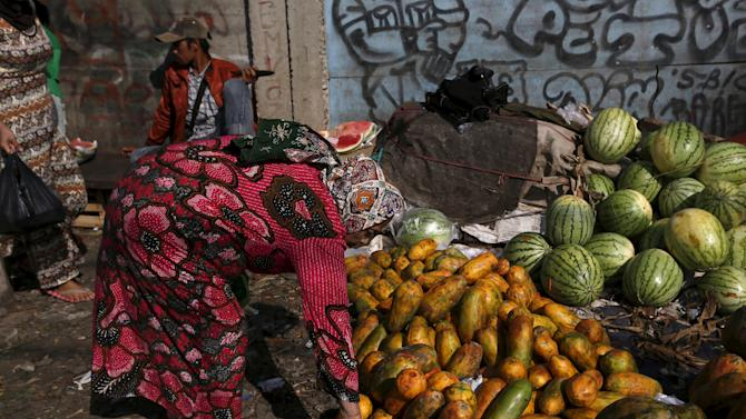A woman holds a papaya to buy it at a vegetable market near Duri train station in Jakarta