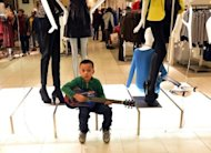 "<p>A boy sits with a toy guitar on a display in Macy's department store after the store opened at midnight on November 23 in New York to start the ""Black Friday"" shopping weekend. The critical shopping day is often what tips retailers out of the red and into the black for the year.</p>"