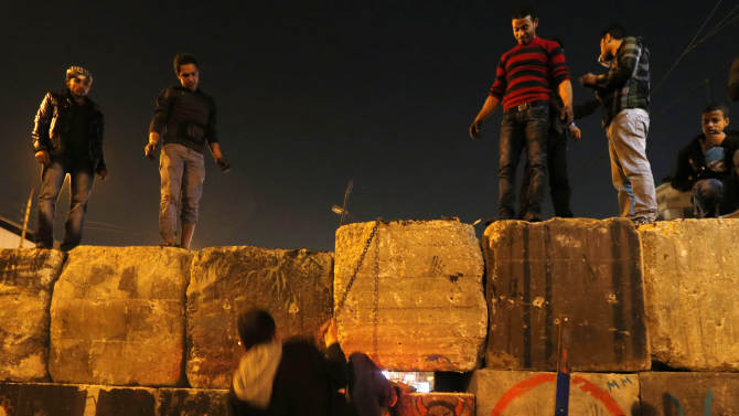 """Protesters dismantle a wall guarding the presidential palace during a demonstration in Cairo, Egypt, Tuesday, Dec. 11, 2012. Arabic writing reads, """"killing me won't bring back your regime."""" Thousands of opponents and supporters of Egypt's Islamist president staged rival rallies in the nation's capital Tuesday, four days ahead a nationwide referendum on a contentious draft constitution. (AP Photo/Petr David Josek)"""
