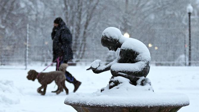 """A man walks his dog past the snow covered """"Boy and Bird"""" fountain in the Boston Public Garden in Boston, Friday, Feb. 8, 2013. Mass. Gov. Deval Patrick declared a state of emergency Friday and banned travel on roads as of 4 p.m. as a blizzard that could bring nearly 3 feet of snow to the region began to intensify. As the storm gains strength, it will bring """"extremely dangerous conditions"""" with bands of snow dropping up to 2 to 3 inches per hour at the height of the blizzard, Patrick said. (AP Photo/Charles Krupa)"""