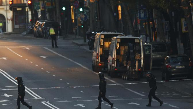 Spanish riot police walk past a bomb detector outside the headquarters of Spain's ruling People's Party (PP) in Madrid