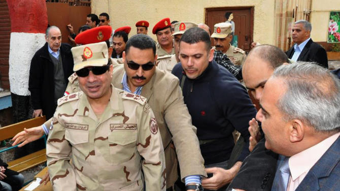 FILE - In this Tuesday, Jan. 14, 2014 file photo released by the Egyptian Defense Ministry, Defense Minister Gen. Abdel-Fattah el-Sissi, left, visits a polling site in the Heliopolis neighborhood of Cairo, Egypt, on the first day of voting in the constitutional referendum. Egypt's state TV said Monday, Jan. 27, 2014 that the country's Interim President issued a presidential decision, promoting the powerful army chief who led the July coup removed Islamist president from power, to the top military rank of marshal. (AP Photo/Egyptian Defense Ministry via Facebook, File)