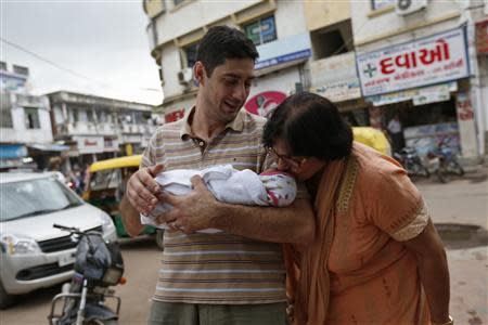 Fabbricatore holds his week-old daughter Gabriella, who is kissed by her maternal grandmother Patel, outside the Akanksha IVF centre in Anand town