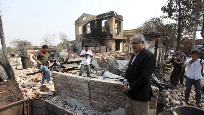 Vijay Nambiar, U.N. Secretary General Ban Ki-moon's special adviser on Myanmar, looks at debris of the buildings destroyed during the ethnic unrest between Buddhists and Muslims in Meikhtila, about 550 kilometers (340 miles) north of Yangon, Myanmar, Sunday, March 24, 2013. The top UN envoy to Myanmar toured a central city Sunday destroyed in the country's worst explosion of Buddhist-Muslim violence this year, calling on the government to punish those responsible for a tragedy that left dozens of corpses piled in the streets, some of them charred beyond recognition.(AP Photo/Khin Maung Win)