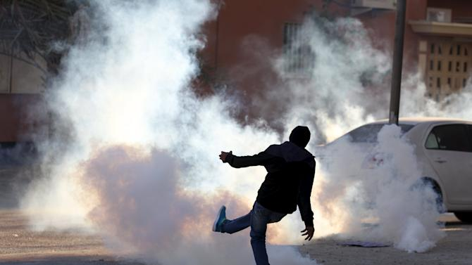 A protester kicks a tear gas canister fired by riot police away from fellow protesters during anti-government clashes in Sitra