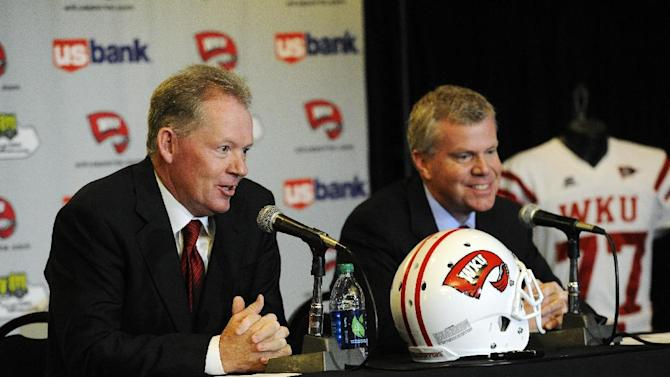 """New Western Kentucky head coach Bobby Petrino, left, responds to a question as athletic director Todd Stewart smiles during an NCAA college football news conference, Monday, Dec. 10, 2012, in Bowling Green, Ky. The 51-year-old was fired by Arkansas in April for a """"pattern of misleading"""" behavior following an accident in which the coach was injured while riding a motorcycle with his mistress as a passenger but now wants to make the most of his second chance. (AP Photo/The Daily News, Joe Imel)"""