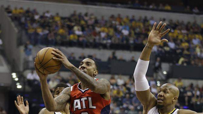 Atlanta Hawks' Jeff Teague (0) shoots against Indiana Pacers' Paul George (24) and David West (21) during the first half of Game 5 in the first round of the NBA basketball playoff series on Wednesday, May 1, 2013, in Indianapolis.  (AP Photo/Darron Cummings)