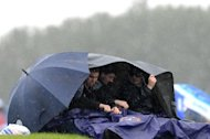 Spectators try to stay dry during the qualifying session at the Silverstone circuit on July 7 ahead of the British Formula One Grand Prix. Silverstone's managing director has vowed to carry on in his job as the circuit started counting the cost of last weekend's rain-marred British Grand Prix