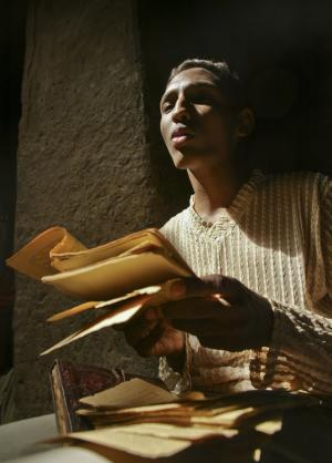 In this photo taken Tuesday, Mar. 16, 2004, Alhousseini Ould Alfadrou, 16, sings verses from crumbling ancient Islamic manuscripts in a mud-walled house in Timbuktu, Mali. Islamist extremists torched a library containing historic manuscripts in Timbuktu, the mayor of the town said Monday, Jan. 28, 2013, while owners have succeeded in removing some of the manuscripts from Timbuktu to save them and others have been carefully hidden away from the Islamists. (AP Photo/Ben Curtis)