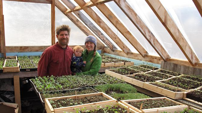 Edge Fuentes, left, stands with his wife Katie Spring, right, and their 9-month-old son Waylon in their planting room surrounded by seedlings for vegetables and flowers at their Good Heart Farmstead, Thursday, April 24, 2014, in Worcester, Vt. Spring and Fuentes back the GMO labeling bill passed by the Vermont Legislature. They believe people need to be able to know what's in their food. (AP Photo/Wilson Ring)