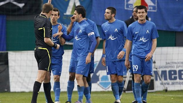 Levski Sofia's players argue with referee Lars Christoffersen (L)