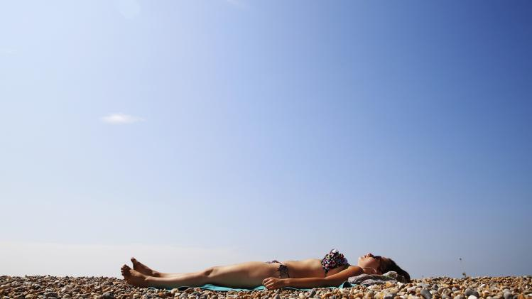 Student Georgina Sapak sunbathes on the beach during a hot summer day by the Brighton pier in southern England