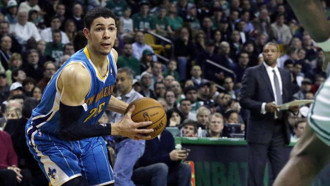 New Orleans Hornets shooting guard Austin Rivers (25) drives to the hoop as his father, Boston Celtics head coach Doc Rivers, background right, watches during the second quarter of an NBA basketball game in Boston, Wednesday, Jan. 16, 2013. (AP Photo/Elise Amendola)