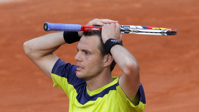 France's Paul-Henri Mathieu holds his racket on his head after defeating USA's John Isner during their second round match in the French Open tennis tournament at the Roland Garros stadium in Paris, Thursday, May 31, 2012. Mathieu won 6-7, 6-4,6-4, 3-6, 18-16. (AP Photo/Christophe Ena)