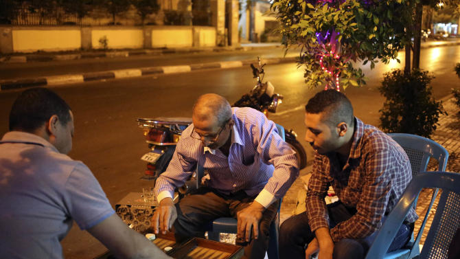 In this Sunday Aug. 25. 2013 photo, Egyptian men play backgammon outside a juice bar hours after a night time curfew went into effect in the Garden City neighborhood of Cairo Egypt. The curfew has been a shock to Cairo, a city where cafes stay packed into the night and parents routinely take their children out for dinners nearing midnight. The military-backed government's curfew, after violent unrest following the July 3 coup that ousted President Mohammed Morsi, slashed the typical Cairo 24-hour life to just 11 hours.(AP Photo/Thomas Hartwell)