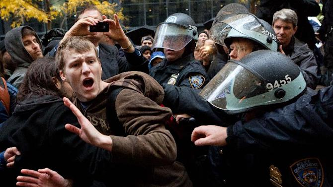 An Occupy Wall Street protestor is grabbed by police as he tries to escape a scuffle in Zuccotti Park, Thursday, Nov. 17, 2011, in New York. Two days after the encampment that sparked the global Occupy movement was cleared by authorities, demonstrators marched through the financial district and promised mass gatherings in other cities. (AP Photo/John Minchillo)