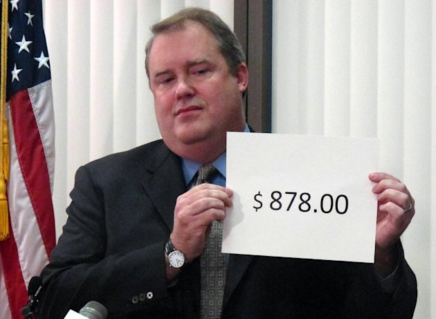 Alaska Revenue Commissioner Bryan Butcher holds up the amount of this year's Permanent Fund Dividend during a news conference Tuesday, Sept. 18, 2012, in Anchorage, Alaska. Butcher announced this year's check from the state's oil riches will be $878 for nearly every single Alaskan. (AP Photo/Mark Thiessen)