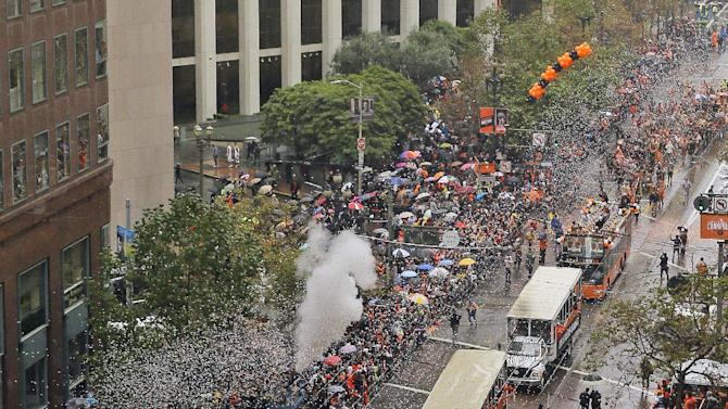 A bus carrying San Francisco Giants baseball players Hunter Strickland and Tim Hudson makes its way down Market Street during a victory parade for the 2014 World Series Champion San Francisco Giants on Friday, Oct. 31, 2014 in San Francisco.  (AP Photo/Eric Risberg)