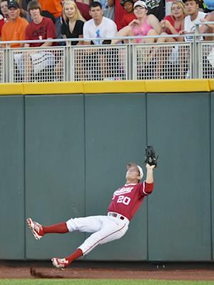 Indiana right fielder Casey Smith falls backward on the warning track as he catches a fly ball hit by Oregon State's Dylan Davis in the fifth inning of an NCAA College World Series elimination baseball game in Omaha, Neb., Wednesday, June 19, 2013. (AP Photo/Ted Kirk)