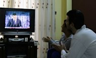 <p>Syrians watch embattled President Bashar al-Assad making a public address on state-run Syrian TV, on January 6, 2013 in Damascus. Assad, speaking to wild applause from ecstatic crowds packed into a cultural centre in Damascus, outlined a plan he said was aimed at resolving the 21-month conflict which according to the UN has claimed more than 60,000 lives.</p>