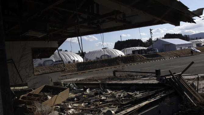 In this Friday, Feb. 22, 2013 photo, a dome-shaped greenhouses are seen near earthquake and tsunami damaged buildings in Rikuzentakata, Iwate Prefecture, northeastern Japan. Few businesses have rebuilt in the worst hit areas of the disaster zone, and uncertainty over prospects for reconstruction is deterring most from outside from even considering investments there. One of the few projects to start up here so far, Granpa Farms, is an agrotechnology company from Kanagawa, near Tokyo, that has built eight dome-shaped high-tech greenhouses for hydroponic farming of lettuce and other greens. (AP Photo/Junji Kurokawa)