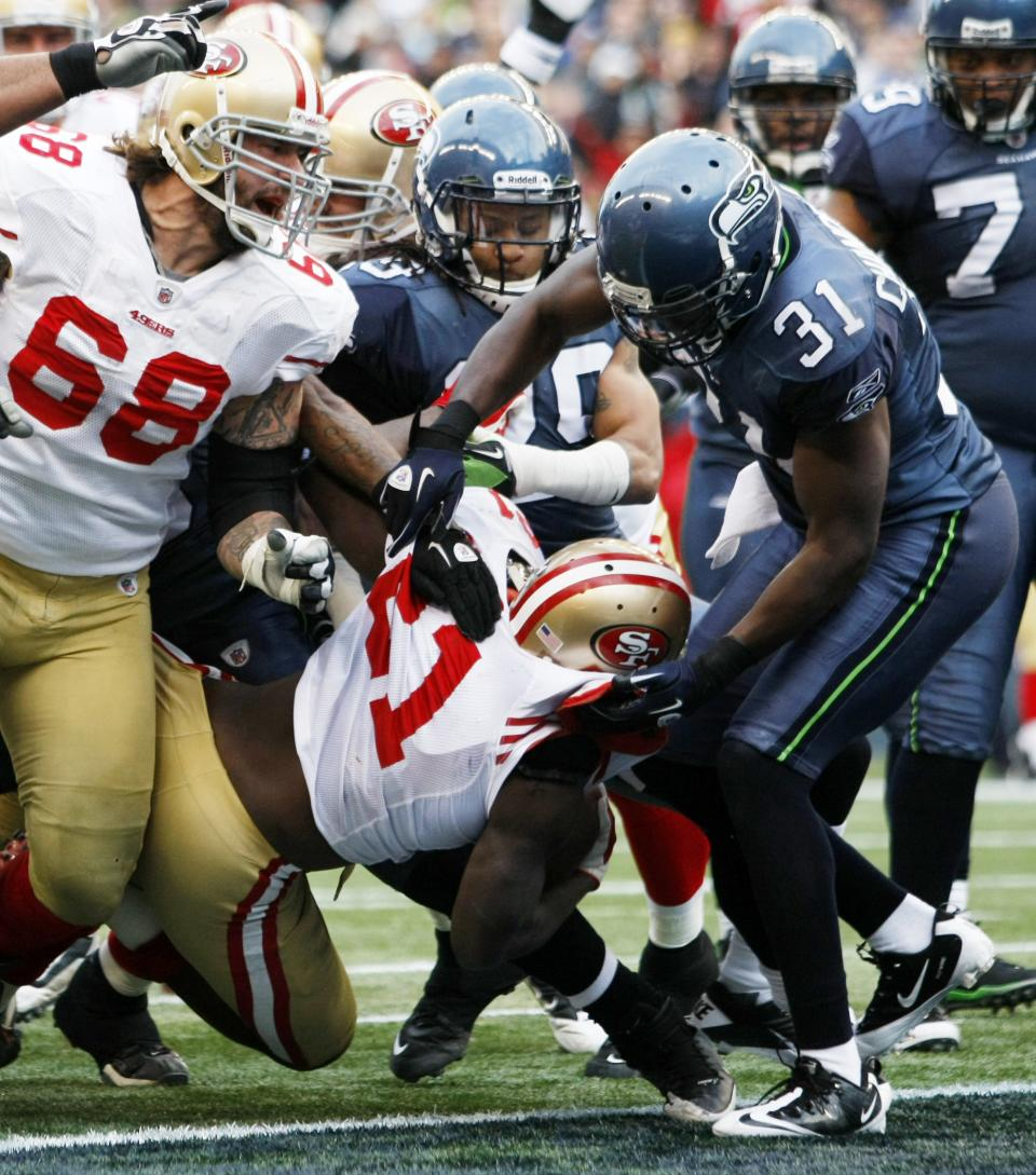 San Francisco 49ers'  Frank Gore scores against the Seattle Seahawks in the first half of an NFL football game in Seattle Saturday, Dec. 24, 2011. (AP Photo/John Froschauer)