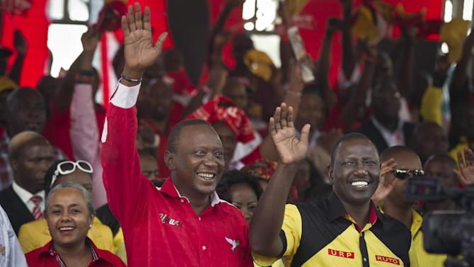 Kenyan Presidential candidate Uhuru Kenyatta, left, and his running mate William Ruto, right, greet the crowd at the final election rally of Kenyatta's The National Alliance party at Uhuru Park in Nairobi, Kenya Saturday, March 2, 2013. Kenya's top two presidential candidates - Uhuru Kenyatta and Raila Odinga - held their final rallies Saturday before large and raucous crowds ahead of Monday's vote, which is the first nationwide election since Kenya's December 2007 vote descended into tribe-on-tribe violence that killed more than 1,000 people. (AP Photo/Ben Curtis)