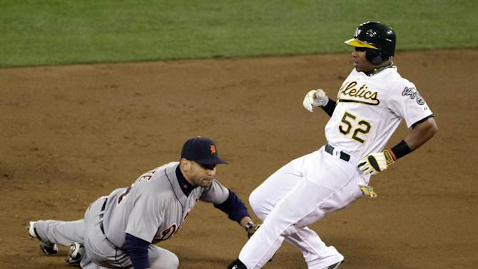 Oakland Athletics Yoenis Cespedes is safe at second after hitting a double as Detroit Tigers second baseman Omar Infante, left, attempts to tag in the first inning of Game 5 of an American League division baseball series in Oakland, Calif., Thursday, Oct. 11, 2012. (AP Photo/Eric Risberg)