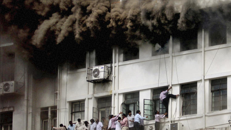 Indian employees are evacuated as smoke billows after the Maharashtra state government caught fire in Mumbai, India, Thursday, June 21, 2012. Hundreds of employees were evacuated Thursday from the seven-story government building as more than two dozen fire engines battled the major fire that raged for more than three hours in India's financial and entertainment capital. (AP Photo)