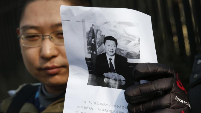Man whose parents were onboard the missing Malaysia Airlines flight MH370, holds a paper during a protest demanding the Malaysian government to keep searching the missing flight, in front of the Malaysian Embassy in Beijing